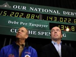 Supporters of Republican presidential candidate Mitt Romney stand next to a national debt clock during a rally Sunday in Exeter, N.H. The debt is projected to surge.