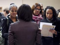 People talk with a recruiter at a job fair sponsored by National Career Fairs in New York last month.