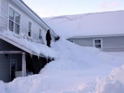 A man stands on a house buried in snow in the fishing town of Cordova, Alaska, on Saturday.