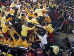 Barefoot Catholic devotees jostle to kiss the Black Nazarene as they gather during its annual festival in Manila, Philippines, on Monday.