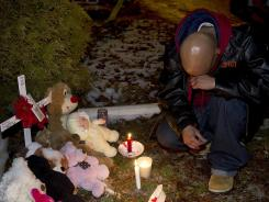 Ron Penn takes a knee in a moment of silence in front of a makeshift shrine Dec. 27 in memory of 9-year-old Aliahna Lemmon at the Northway mobile home park in Fort Wayne, Ind.