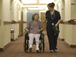 Cedar Village resident Mildred Klein is escorted down a hallway with nurse's aide Katie Palumbo. Mildred is not an abuse victim.