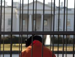 Beth Brockman of Witness Against Torture sits in a cage during Tuesday's demonstration outside the White House, urging the government to close Guantanamo prison.