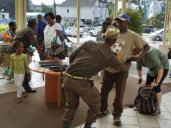 Guards search shoppers entering the Yaya Centre mall Tuesday in Nairobi, Kenya.