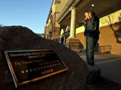 Memorial plaque:  Janet Putnam at the site of the Tucson shooting a year ago.