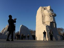 Alma Deveaux photographs her husband, Perry, on Thursday at the Martin Luther King Memorial.