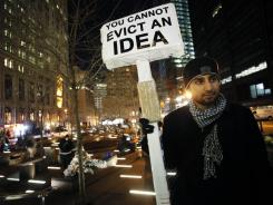 Adam Farooqui holds a sign as he stands at Zuccotti Park on Wednesday in New York.