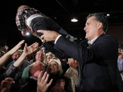 Mitt Romney hands a baby back to an audience member as he campaigns Wednesday in Columbia, S.C.
