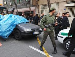 Iranian security forces stand guard around the site of an explosion Wednesday outside a university in Tehran.