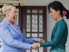 In this photo taken Dec. 2, 2011, Aung San Suu Kyi, right, and Hillary Clinton react after speaking to the press in Rangoon.