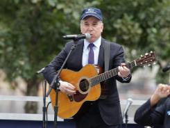 Paul Simon performs at Ground Zero during a 10th anniversary ceremony of the 9-11 terrorist attacks. Simon says he has many questions about God and explores them through his music.