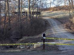Crime scene tape blocks the driveway at the home of Paul Gilkey, about 5 miles north of Logan, Ohio, on Tuesday. Gilkey's wife, Darlene Gilkey, died days after her husband fatally shot their adult son and her two sisters in front of her and then killed himself.