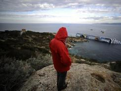 An Isola di Giglio citizen looks at the Costa Concordia on Sunday after the cruise ship keeled over. At least five people died in the wreck off the Tuscan coast.
