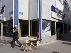 A security guard, right, stands at the entrance of the national Israeli air carrier El Al sales offices in Tel Aviv, Israel, on Monday.