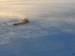 The Russian tanker Renda sits off Nome's coast Monday with two fuel transfer hoses running to a causeway in a harbor.