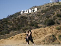 Two women hike in Griffith Park Wednesday near the Hollywood sign after a plastic bag containing a human head was discovered Tuesday.