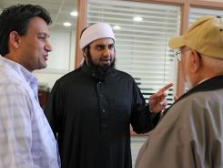 Imam Asif Umar, center, talks with Amil Rajput, left, and Syed Rahman following Friday prayers at the Daar-ul-Islam mosque in St. Louis.