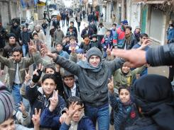 Anti-Syrian regime protesters chant slogans and flash the victory sign as they march during a demonstration on Tuesday in Zabadani, Syria.