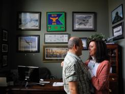 Col. Jim Ravella and his wife, Ginger, share a quiet moment in their home office. The posters, artwork and mementos hanging on the wall are a mix of both Ginger's current and first husband - both Air Force pilots.