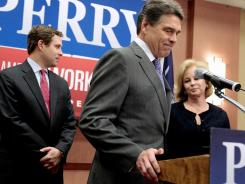 Texas Gov. Rick Perry announces the end of his presidential campaign in North Charleston, S.C., on Thursday as his son, Griffin, and wife, Anita, look on.