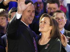Rick Santorum greets supporters with his wife Karen in Johnston, Iowa, on Jan. 3. Certification of Iowa's contest shows him as the leader.