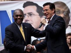 Comedian Stephen Colbert shakes hands with former Republican presidential candidate Herman Cain during a Friday rally at the College of Charleston.