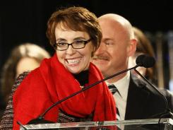 Rep. Gabrielle Giffords and husband Mark Kelly attend a vigil remembering victims and survivors of the Tucson, Ariz.., shooting.
