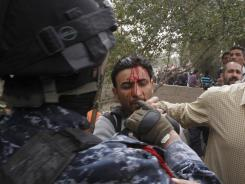 An Iraqi officer, left, hits and detains journalist Mohammed al-Rased during a demonstration in Basra, Iraq, on March 4, 2011. Iraq's government has cracked down harshly on dissent during the past year of Arab Spring uprisings.