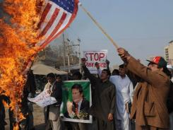 A Pakistani protester holds a burning U.S. flag during an anti-drone demonstration in Multan on Jan. 11. More missiles were reported fired.