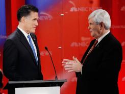 Mitt Romney and Newt Gingrich talk during a commercial break at Monday's GOP presidential debate in Tampa.
