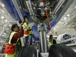 Boeing workers examine the front landing gear for a 787 plane in 2009 in Everett, Wash.