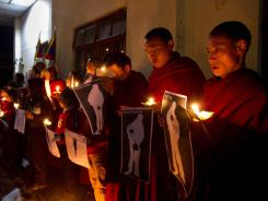 Tibetan Buddhist monks hold pictures of Tibetans they claim were allegedly shot by Chinese security forces earlier this week, during a candlelight vigil in Dharamsala, India, on Wednesday.
