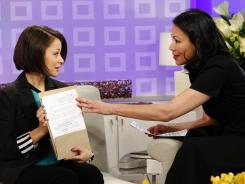 In this image released by NBC, science whiz kid Samantha Garvey shows Today co-host Ann Curry her copy of the state of the union speech autographed by President Obama.