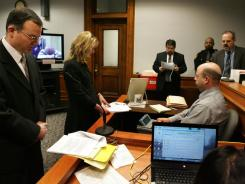 Defense attorneys Brian Pierce, left, and Rhonda Kotnik listen to assistant prosecutors read 27 indictments against Richard Beasley in Summit County Court on Wednesday in Akron, Ohio.