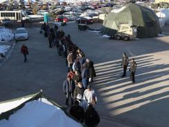 Homeless U.S. military veterans stand in line to receive free services at an event hosted by the Department of Veterans Affairs on November 3, 2011, in Denver.