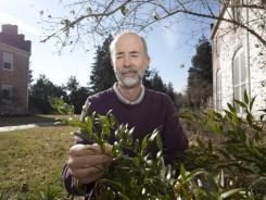 Steve Carroll, director of public programs at the State Arboretum of Virginia in Boyce, Va., works with a rosemary plant.
