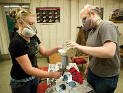 Beth Leck, left, and Kelsea DeBowes mix paint at the Babson-Carpenter Career and Technical Education Center in Hayden, Colo., last year.