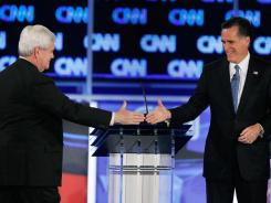 Republican presidential candidates Newt Gingrich and Mitt Romney greet one another before the start of Thursday's debate in Jacksonville, Fla.