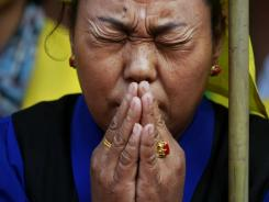 An exiled Tibetan woman prays at a rally Sunday in New Delhi, India, to show solidarity with Tibetans who have either died by self-immolation or were allegedly killed in Chinese police firing.