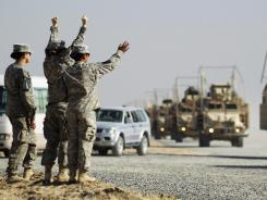 U.S. soldiers at the Kuwait border wave to colleagues who are part of the last military convoy to leave Iraq on Dec. 18, 2011.