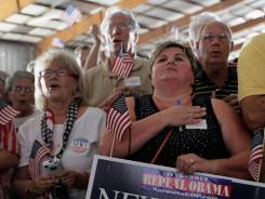 People recite the Pledge of Allegiance as they wait to hear Newt Gingrich speak during a campaign event Wednesday in Sarasota, Fla.