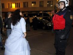 A woman in a ball gown passes a police officer during a protest Friday outside Vienna's Hofburg palace.