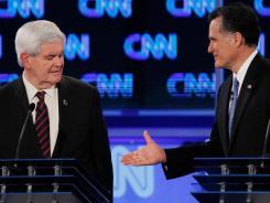 Newt Gingrich Mitt Romney shake hands at the end of a debate in Florida.