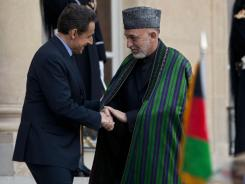 French President Nicolas Sarkozy, left, welcomes Afghan President Hamid Karzai, right, Friday at the Elysee Palace in Paris.