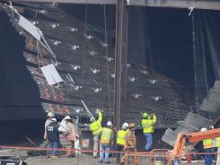 Workers and officials inspect the scene of a collapse at the Horseshoe Casino under construction in Cincinnati.