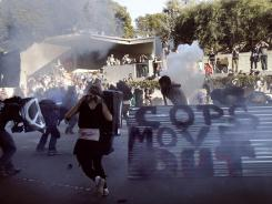 Oakland police deploy smoke and tear gas to stop protesters with the Occupy Oakland camp as they march through downtown Oakland on Saturday.