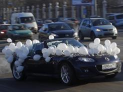 Cars with white ribbons or white balloons drive around Moscow's Garden Ring Sunday in a show of support for a movement against Russian Prime Minister Vladimir Putin.