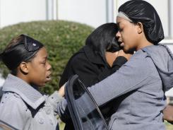 Ravenn Carlton, center, wife of one of the victims, is comforted by Nakia Carlton, left, and Khalena Carlton near the house where five people were found dead in Birmingham, Ala., on Sunday.