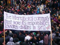Anti-government Syrian protesters hold a sign during a demonstration in the southern city of Daraa on Saturday.