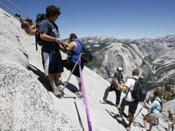 Climbers on the cable section of Half Dome negotiate the steep granite pitch in Yosemite, Calif.